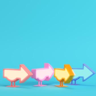 Cztery kolorowe billboardy w kształcie strzałki na jasnoniebieskim tle w pastelowych kolorach