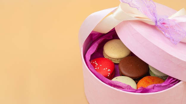 Cztery kolorowe francuskie makaroniki w różowym kartonie na brzoskwiniowym tle. wolne miejsce