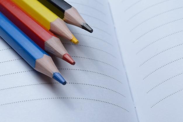 Cztery kolorowe kredki - niebieski, czerwony, żółty, czarny. leżeć na otwartym notatniku.