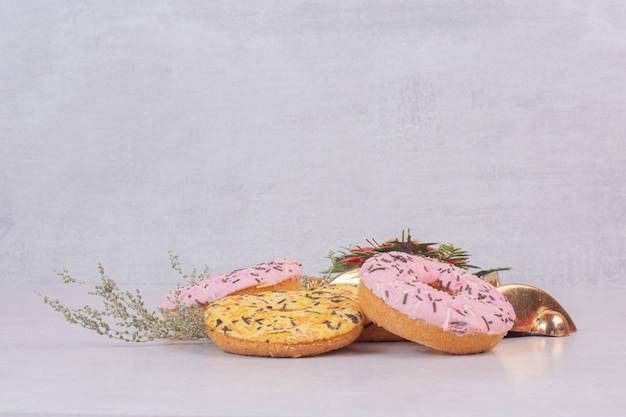 Cztery kolorowe słodkie pączki na białej powierzchni