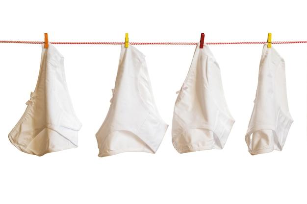 Cztery majtki damskie na bielizny na białym tle. suszenie ubrań po praniu.