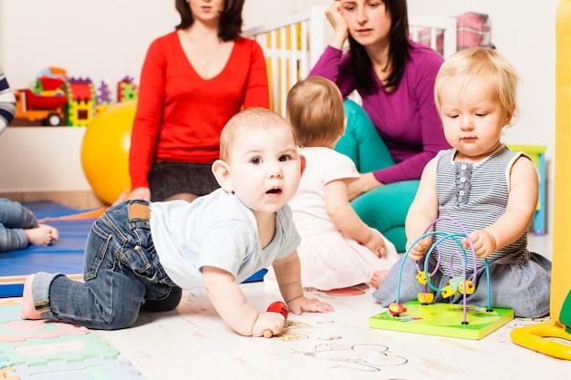 Cztery mamy ze swoimi uroczymi dziećmi w przedszkolu