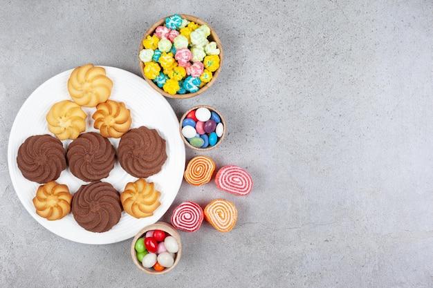 Cztery marmolady, trzy miski cukierków i talerz różnorodnych ciasteczek na marmurowym tle. wysokiej jakości zdjęcie
