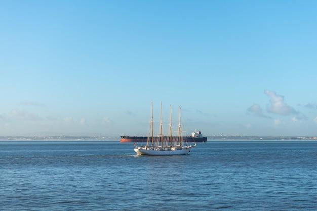 Cztery maszty żaglowiec i statek towarowy na morzu