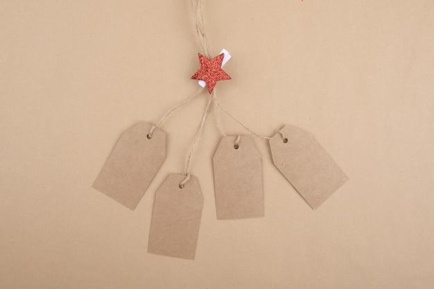 Cztery metki z przetworzonego papieru pakowego zwisające z liny ozdobionej spinaczem do bielizny z czerwoną gwiazdą bożonarodzeniową