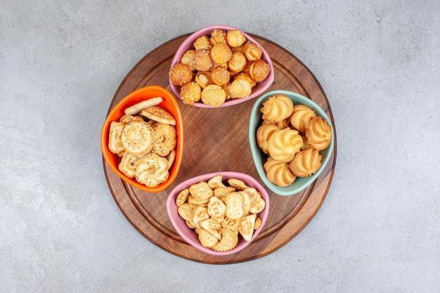 Cztery miski herbatników i chipsów na drewnianej desce na marmurowej powierzchni.