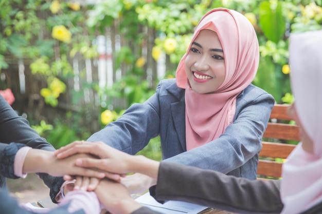 Cztery młoda kobieta biznesu łącząc ręce
