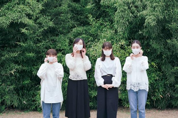 Cztery młode japonki ubrane w białe koszule i maski na zewnątrz
