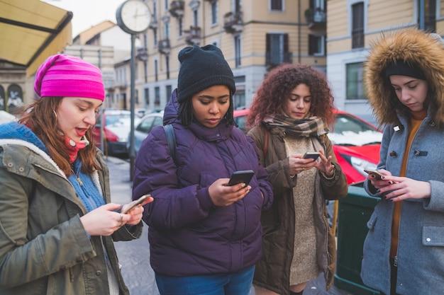 Cztery młode kobiety używa smartphone