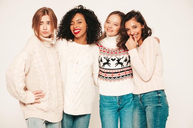 Cztery młode piękne uśmiechnięte hipster dziewczyny w modnych zimowych swetrach. pozytywne modele bawiące się i przytulające