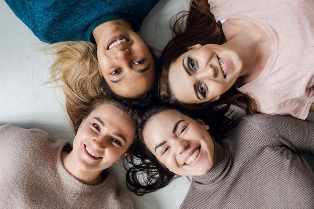 Cztery najlepsze przyjaciółki rozmawiają w domu dziewczyny spędzają razem czas i bawią się wysokiej jakości zdjęciami