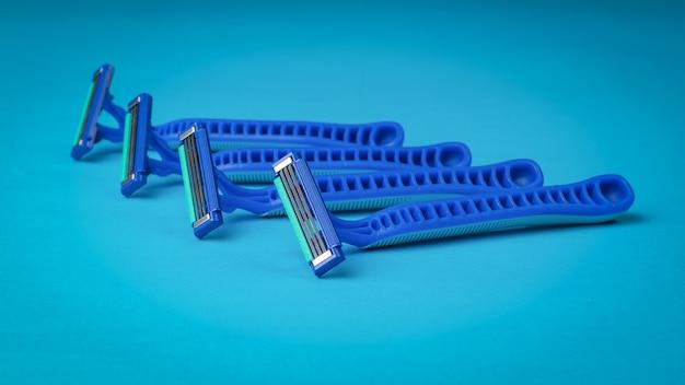 Cztery niebieskie jednorazowe maszynki do golenia na niebieskiej powierzchni. narzędzia do pielęgnacji twarzy. zestaw do pielęgnacji męskiej twarzy.