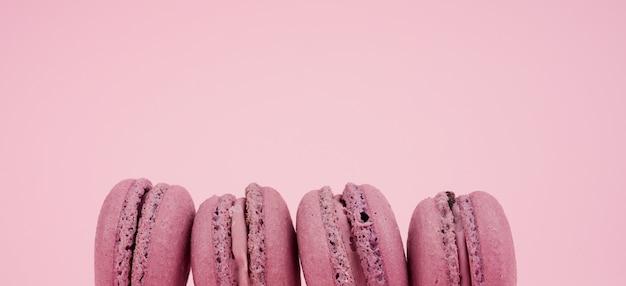 Cztery okrągłe fioletowe makaroniki z mąki migdałowej z kremem