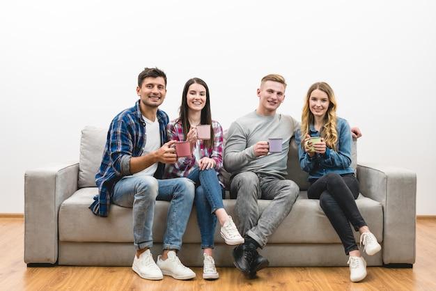 Cztery osoby z filiżankami siedzą na kanapie na białym tle ściany