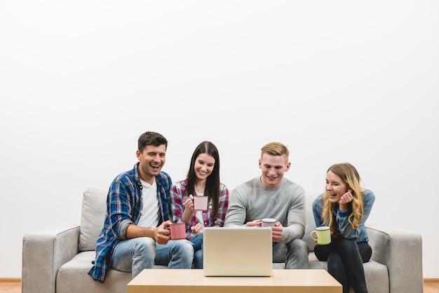 Cztery osoby z filiżankami siedzą obok laptopa na tle białej ściany