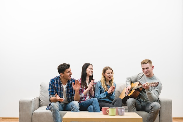 Cztery osoby z gitarą siedzą na kanapie na białym tle ściany