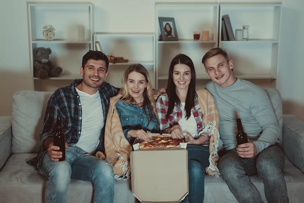 Cztery osoby z pizzą i piwem oglądają film na kanapie