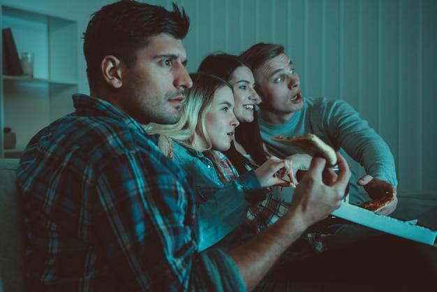 Cztery osoby z pizzą oglądają film na kanapie