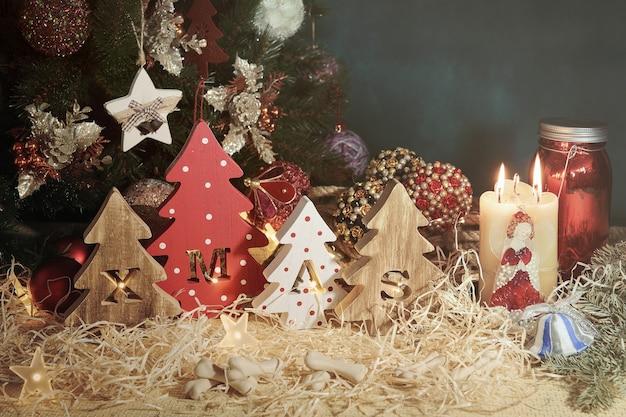 Cztery ozdobne, drewniane choinki z wyrzeźbionymi literami bożonarodzeniowymi i delikatnością w postaci kosteczek dla czworonogów. poziomy.