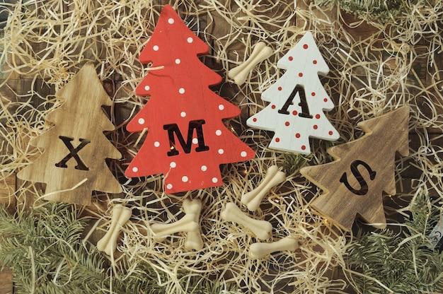 Cztery ozdobne, drewniane choinki z wyrzeźbionymi literami bożonarodzeniowymi i delikatnością w postaci kosteczek dla czworonogów.