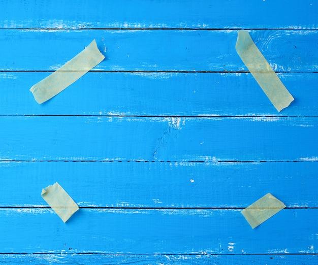 Cztery papierowe żółte kawałki taśmy klejącej przymocowane w rogach do niebieskiej drewnianej powierzchni