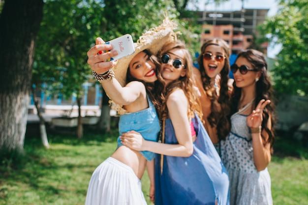 Cztery piękne dziewczyny hipisi robi selfie na zewnątrz