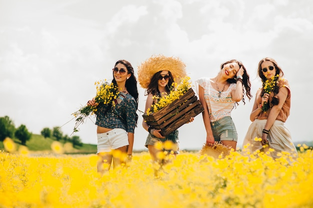 Cztery piękne dziewczyny hippie w polu żółte kwiaty