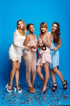 Cztery pięknej dziewczyny odpoczywa przy przyjęciem nad błękit ścianą