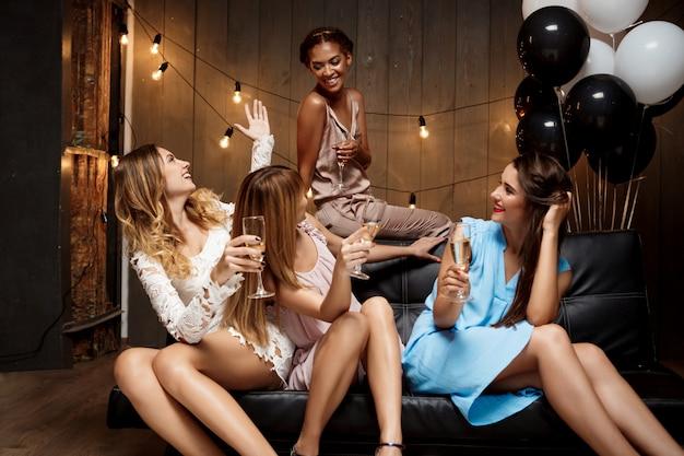 Cztery pięknej dziewczyny odpoczywa przy przyjęciem.