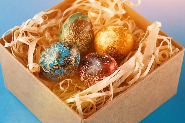 Cztery pisanki pomalowane na czerwono, niebiesko, zielono i żółto leżą w pudełku, w którym znajdują się wióry drewniane. malowane pisanki na niebieskim tle. ścieśniać