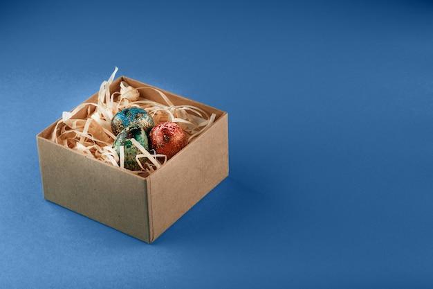 Cztery pisanki pomalowane na czerwono, niebiesko, zielono i żółto leżą w pudełku, w którym znajdują się wióry drewniane. malowane pisanki na niebieskim tle. skopiuj miejsce