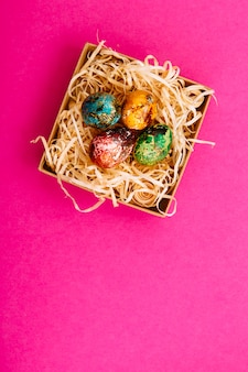 Cztery pisanki pomalowane na czerwono, niebiesko, zielono i żółto leżą w pudełku, w którym znajdują się wióry drewniane. malowane pisanki na różowym tle. leżał płasko. skopiuj miejsce
