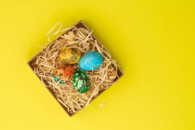 Cztery pisanki pomalowane na czerwono, niebiesko, zielono i żółto leżą w pudełku, w którym znajdują się wióry drewniane. malowane pisanki na żółtym tle. leżał płasko. skopiuj miejsce
