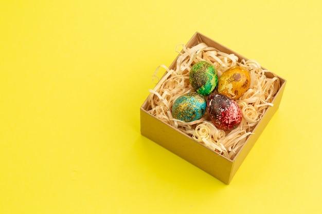 Cztery pisanki pomalowane na czerwono, niebiesko, zielono i żółto leżą w pudełku, w którym znajdują się wióry drewniane. malowane pisanki na żółtym tle. skopiuj miejsce