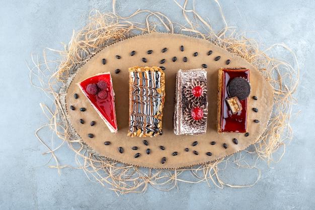 Cztery plasterki różnych ciast na kawałku drewna. zdjęcie wysokiej jakości
