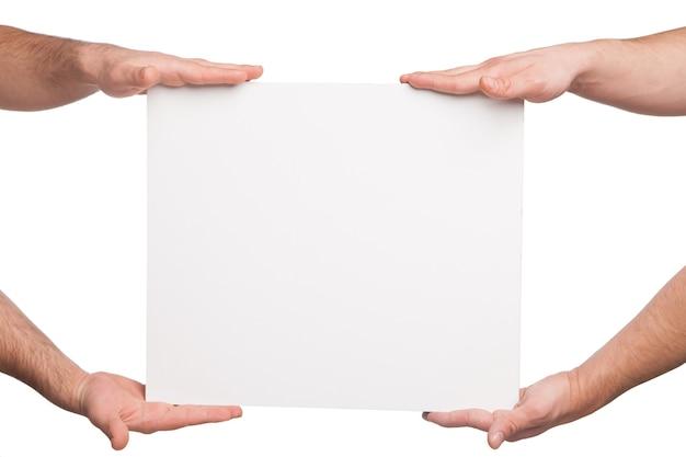 Cztery ręce trzymając pustą białą deskę. na białym tle