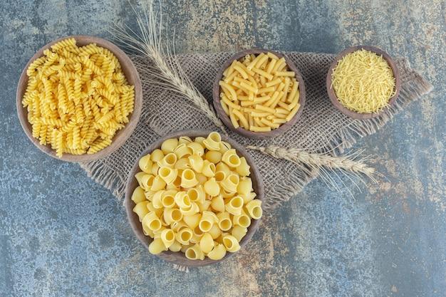 Cztery rodzaje makaronów w miseczkach, na marmurowym tle.