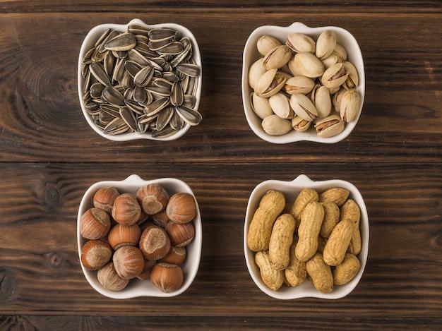 Cztery rodzaje orzechów i nasion w białych miseczkach na drewnianym stole. mieszanka orzechów i nasion. leżał na płasko.