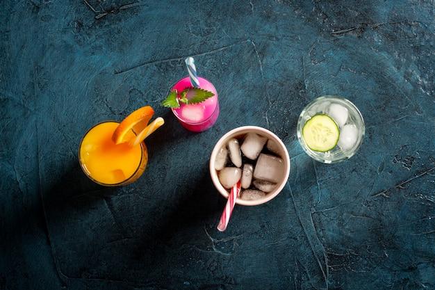 Cztery rodzaje orzeźwiających napojów z lodem na ciemnoniebieskim tle i kostkami lodu. koncepcja klub nocny, nocne życie, impreza, pragnienie. pomarańcza, mięta i ogórek, truskawka, cola. leżał płasko, widok z góry