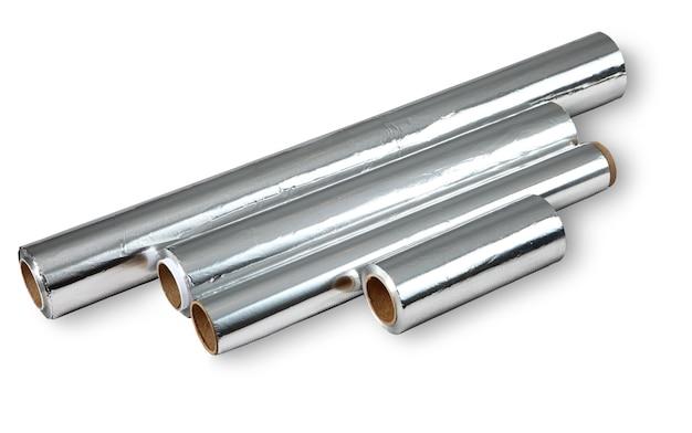 Cztery różne rolki folii aluminiowej do przechowywania żywności i gotowania, na białym tle obraz na białym tle. rolki folii o różnych wymiarach: długości i grubości. żadnego ciała.