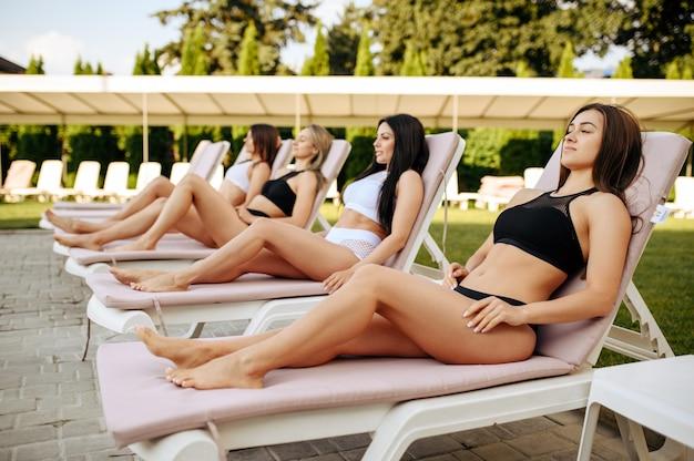 Cztery seksowne kobiety wypoczywają na leżakach przy basenie. piękne dziewczyny relaksują się przy basenie w słoneczny dzień, letnie wakacje atrakcyjnych dziewczyn