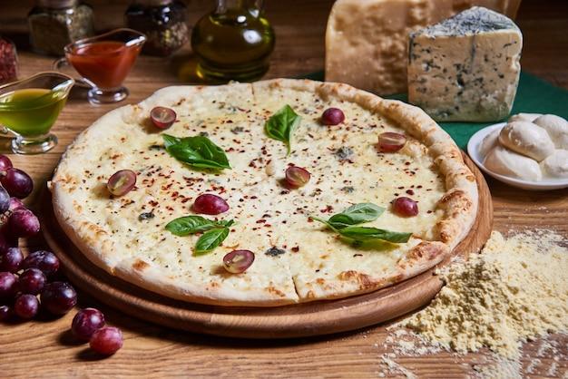 Cztery serowe pizze quattro formaggi z liściem bazylii na rustykalnej desce