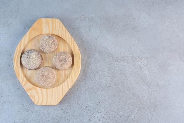 Cztery smaczne kulki z trufli umieszczone na drewnianym talerzu.