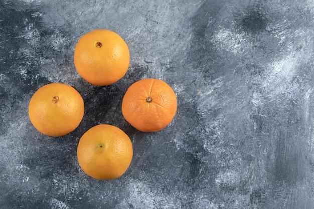 Cztery smaczne pomarańcze na marmurowym stole.