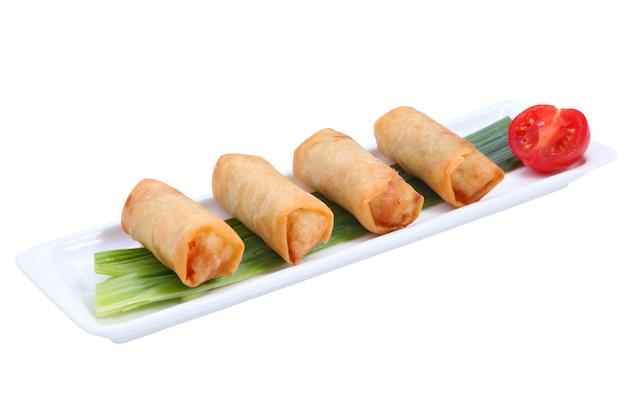 Cztery smażone chińskie sajgonki z rzędu na białym, długim, wąskim porcelanowym talerzu, ozdobionym łodygą zielonej cebuli i pół pomidora, odizolowane na białym tle.