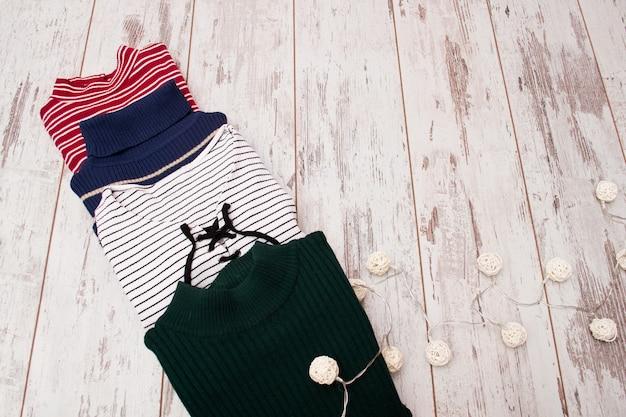 Cztery swetry na drewnianej powierzchni
