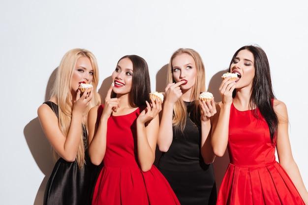 Cztery Szczęśliwe Urocze Młode Kobiety Stojące I Degustujące Babeczki Na Białym Tle Premium Zdjęcia