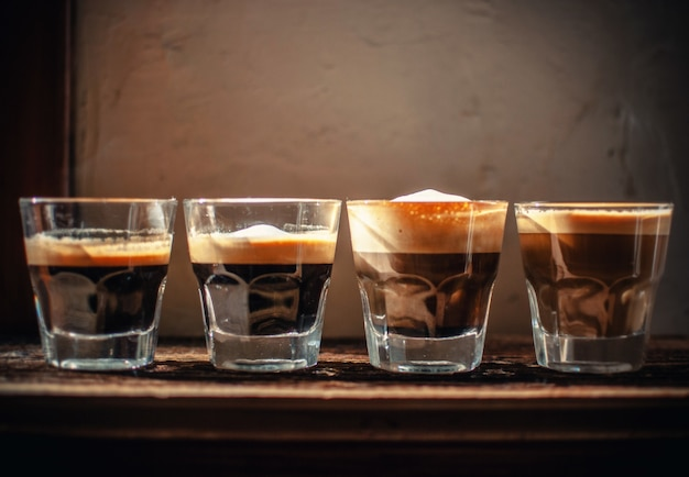 Cztery szklanki z likierem ustawione w rzędzie