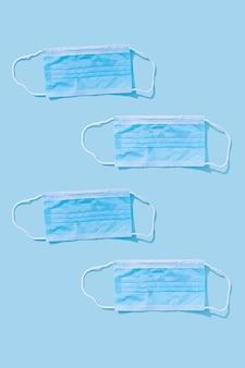 Cztery sztuki masek medycznych na niebieskim tle do ochrony jamy ustnej i nosa przed wirusami i bakteriami. koncepcja epidemii. jednolity wzór, układanie na płasko.
