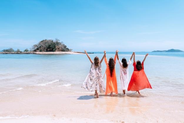 Cztery urocze dziewczyny w kolorowych tunikach stoją na plaży, trzymając się za ręce, trzymając się nawzajem. letnie wakacje na tropikalnej plaży.